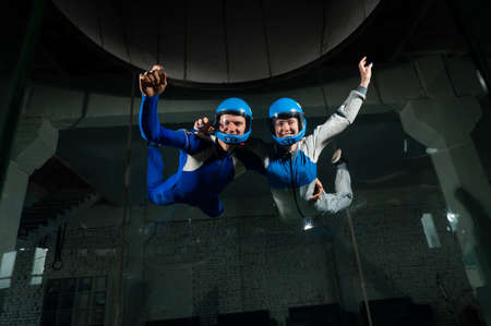 A man and a woman enjoy flying together in a wind tunnel. Free fall simulator