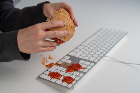 A faceless woman is eating a burger and dripping ketchup on the keyboard 写真素材