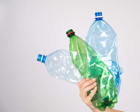 Close-up of a female hand holding a plastic bottles on a white background. 写真素材