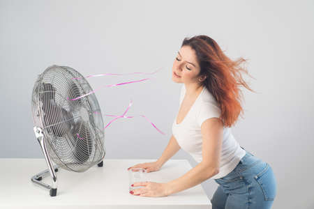 A red-haired Caucasian woman chills by the electric fan and drinks a cold drink. Climate control in the apartment 写真素材