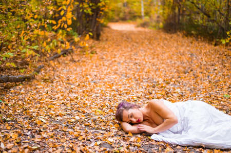 Caucasian woman lies in the autumn forest under a blanket. Nude girl in a leaf fall