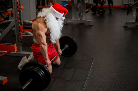 Santa claus in the gym. Muscular man with a naked torso doing exercises with dumbbells.