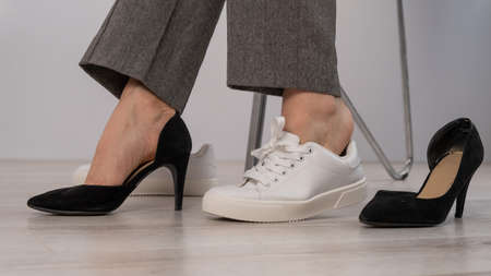 Close-up business woman takes off her shoes puts on white leather sneakers. 写真素材