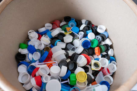 A close-up of many plastic bottle caps collected for recycling.