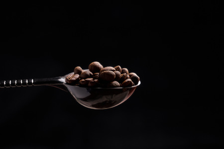 A spoonful of coffee beans in a black background Banco de Imagens