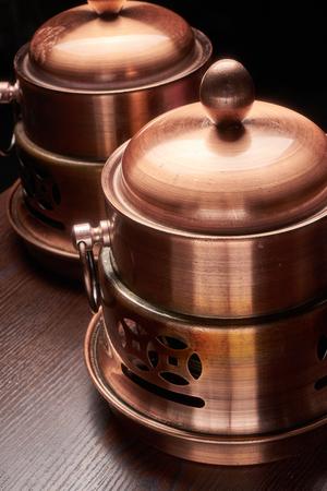 Copper pot on black background