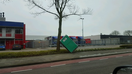 blown away: A mobile toilet was blown away by the storm. Saved by the tree Stock Photo