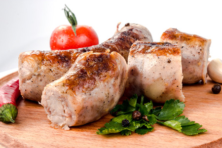 fried pork sausages on white background with cherry tomatoes and hot peppers