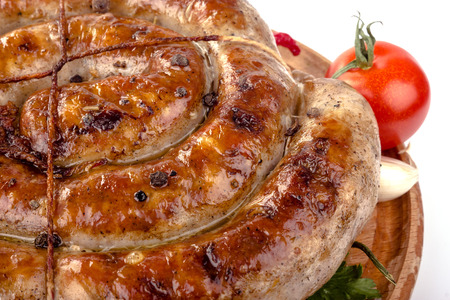 fried pork sausages on a wooden plate with cherry tomatoes and hot peppers Stock Photo