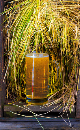 beer glass in an old box with straw on a wooden table