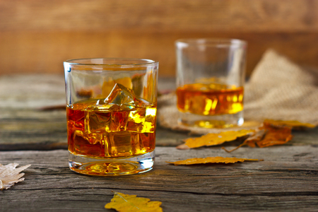 glass of whiskey with ice on a wooden table with oak leaves Stock Photo