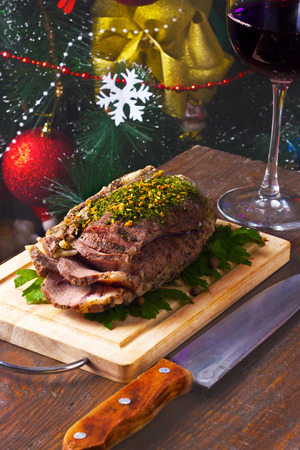 cold boiled pork on a wooden board with a glass of red wine on the background of Christmas tree