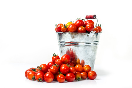 Homemade tomatoes in a bucket on a white background for isolation Stock Photo