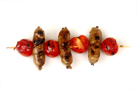 sausages and cherry tomatoes grill on a spit on a white background for isolation