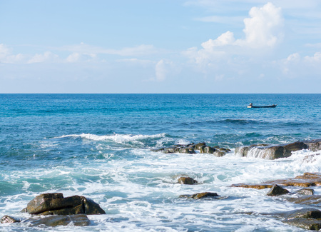 Fisherman drive long tail boat in calm sea and Sea wave rolling on the coast rocks at Koh Kood,Thailand