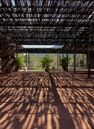 Shadow pattern on textured floor in terrace with bamboo roof structure and plants on background. Siem Reap Province, Cambodia.