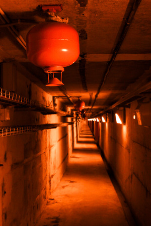 Psychedelic red deep in underground tunnel. Colored industrial background. Emergency lighting, row of fire extinguishers and cable telecommunication rack.
