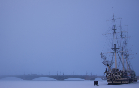 Foggy winter view of the frigate nearby Petrovskaya embankment and frozen Neva river covered with snow and  the Trinity Bridge background. St. Petersburg, Russia.