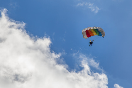 Parachuting, skydiver descends by parachute through the clouds