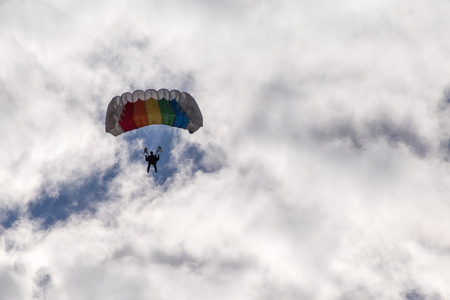 descends: Parachuting, skydiver descends by parachute through the clouds