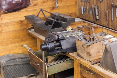 vise: Old workshop with workbench, vise and other hand tools. Open drawer, tool box, wooden table