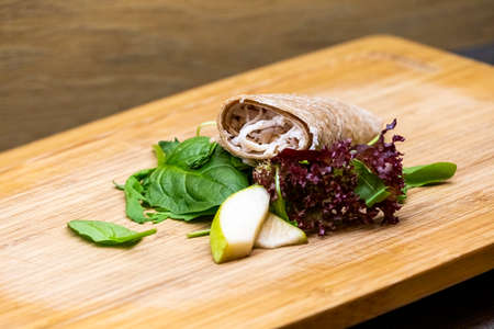 Wholemeal wrap with goat cheese, pear and salad. Fresh healthy food, snack on wooden background 写真素材