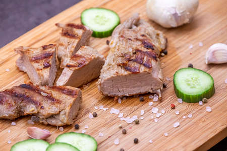 Grilled pork tenderloin cut on a wooden board. Grilled meat with cucumber, garlic and salt