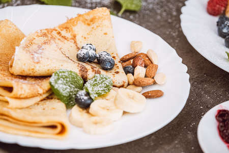 Pancakes with nuts, blueberries, banana and mint leaves. Close-up on a served plate with sweet dessert.