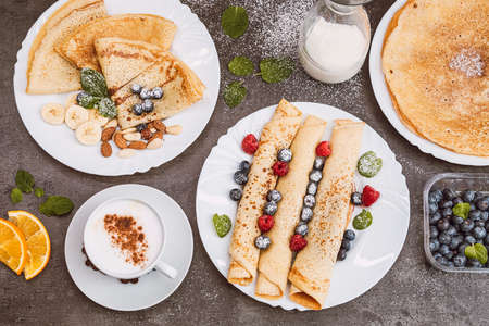 Pancakes with berries and nuts with coffee and milk. View from above. Sweet breakfast, dessert served on a dark background