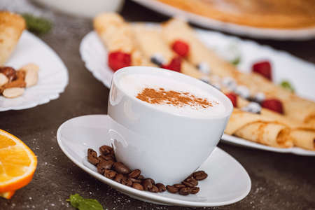 Cup of cappuccino coffee with coffee beans. In the background served pancakes with fruit