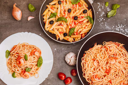 Traditional Italian food. Pasta with tomato sauce, basil, parmesan, olives. Food in a pan and on a plate. View from above.