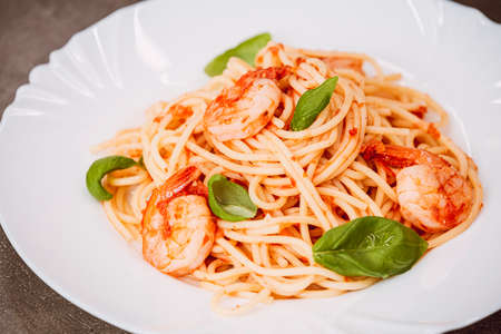 Spaghetti with tomato sauce, basil and shrimps. Italian cuisine. Fresh healthy light main course, serving on a plate
