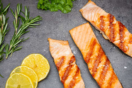 Grilled salmon fish, three pieces of salmon, lemon, rosemary and parsley on a dark background. Top view. Healthy eating 写真素材