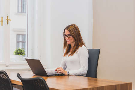 Attractive businesswomen working on a laptop at her workstation. Woman sitting in the office