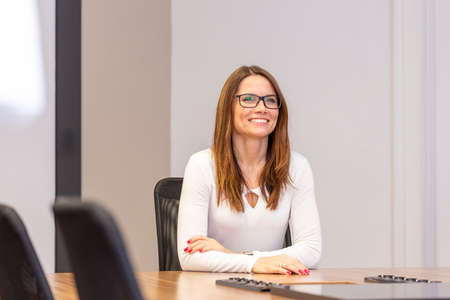 Attractive smiling businesswomen listening in the office. Woman sitting at the table in the office