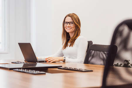 Attractive businesswoman working on a laptop at her workstation. Woman sitting in the office