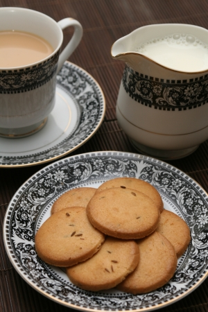 Plate full of biscuits served with milk pot and a cup of tea Stock Photo