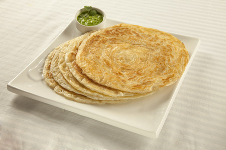 Plain paratha puri served with freshly diced corriander in green chutney Stock Photo