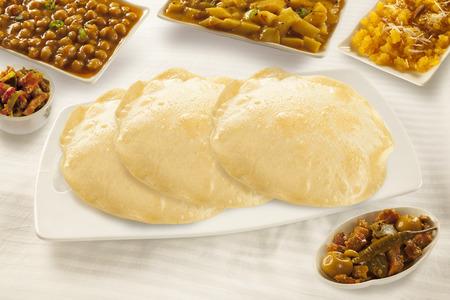 ひよこ豆と甘いハルヴァとピクルスとプリ パラタ 写真素材