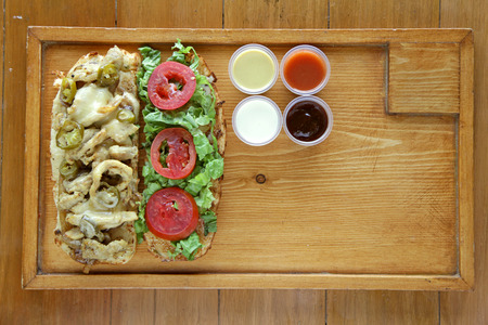 Open face healthy meat and vegetable sandwich served with condiment sauces on a wooden tray