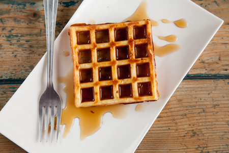 Waffle with maple syrup fork plate top angle