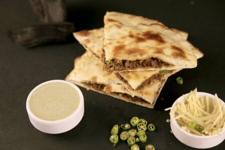 Smoked Minced Meat Stuffed Naan with Green Chillies on Black background with Coal 写真素材