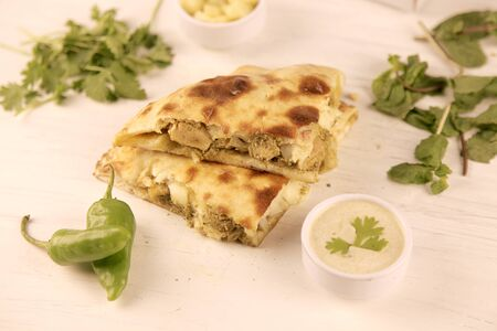 Healthy Stuffed naan desi pizza with herbs vegetables, dips and cheese