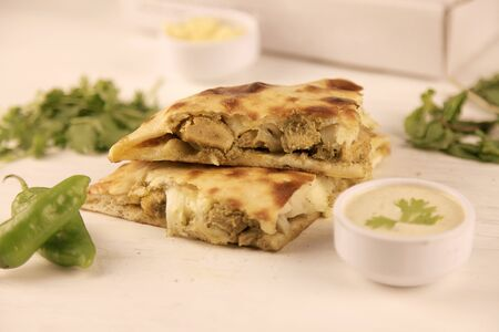 Stuffed naan desi pizza with herbs vegetables, dips and cheese 写真素材