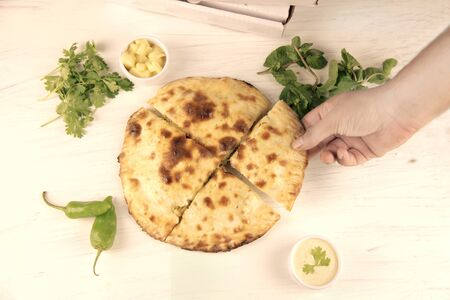 Stuffed naan desi pizza with herbs vegetables and dips.
