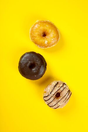 Assorted and colourful gourmet doughnuts on a vibrant yellow background