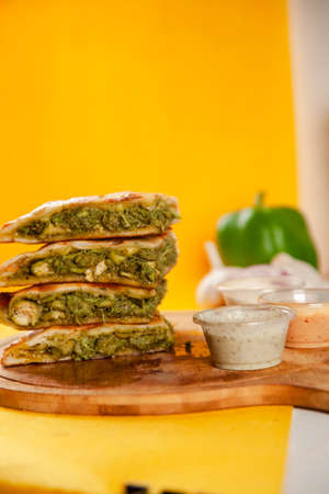 Green chicken tikka stuffed naan cooked in a wood fired oven, food fusion.