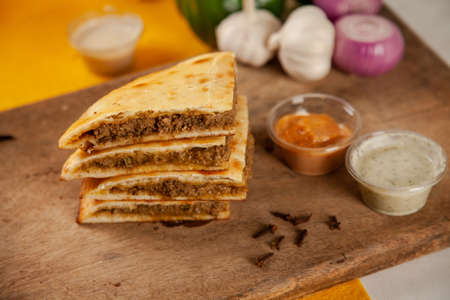 Stuffed minced meat qeema naan with spicy sauces and ingredients 写真素材