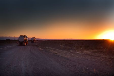 two trucks on the road at sunrise with a blue sky  Stock Photo
