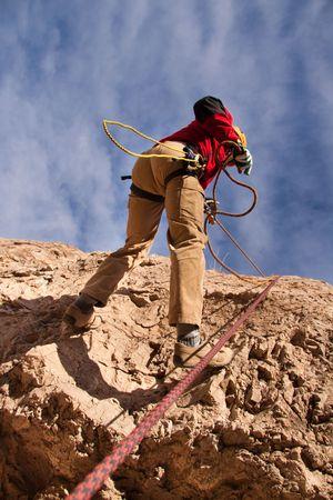 Man climbing a mountain in the blue sky Stock Photo